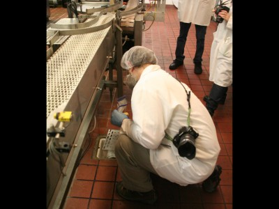 Epidemiologists swab floor drains in the milk processing facility.