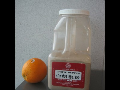 An orange added to illustrate the actual size of a 5lb. container of ground pepper.