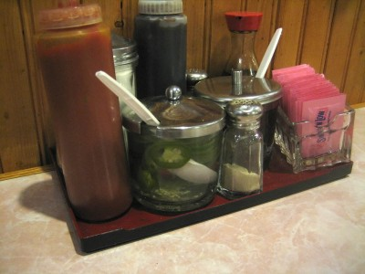 Tray of accoutrements for Phở (Vietnamese noodle soup) including a shaker of the infamous Lian How white pepper.